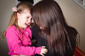 Crying little girl being comforted by her mother — Stock Photo