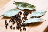Bay leaf with black pepper corn on wooden deck — Stock Photo