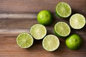 Fresh cut limes on wooden background — Stock Photo