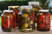 Glass jars of homemade canned tomatoes and cucumbers on the outdoors kitchen — ストック写真