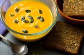 Pumpkin soup in a bowl with seeds and fried bread — Stock Photo