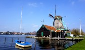 Windmills and river and boat in holland — Stock Photo