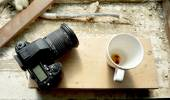 Camera and coffee cup — Stockfoto