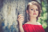 Portrait of a beautiful young  girl in a red dress outdoors — Stock Photo