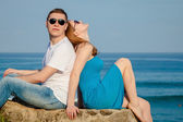 Loving couple sitting on the beach at the day time. — Stock Photo