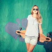 Fashion lifestyle, Beautiful young blonde woman with skateboard — Stock Photo