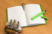 Notebook with green pen and seashells on the desk — Stock Photo