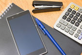 Phone background calculator and stapler and pen on the table — Stock Photo