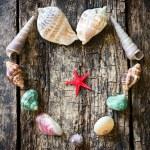 Heart of seashells, shells, shells, sea stars on a wooden table selective focus — Stock Photo #78006328