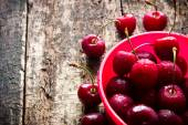 Rural berry cherry with drops of water in a red bucket on a wooden table close-up selective focus — Stock Photo