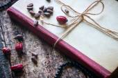 Corded book with beads, dogrose, pine nuts — Stock Photo