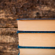Three old books in a stack vertically on a wooden background — Stock Photo #78694558