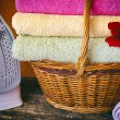 Basket with colored towels red flower, iron, vignetting filter on the wooden background — Stock Photo #79617238