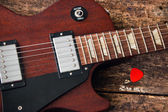 Les Paul electric guitar with a pick on a red wooden background — Stock Photo