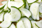 Sliced cucumber stack on wooden plate — Stock Photo