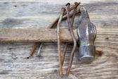 Velhos pregos enferrujados e martelo no fundo de madeira — Fotografia Stock