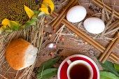 Ears of wheat , tea , cup, sunflower , eggs and bread on burlap — Stock Photo