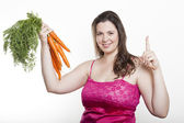 Woman with carrots holds up forefinger — Stock Photo