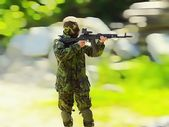 Airsoft boy with ak47, very hard blurred background — Stock Photo