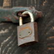 Old Wooden door locked with rusty padlock — Stock Photo #69329141