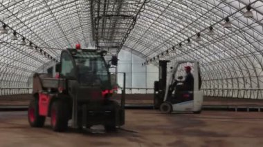 Two tractors lifts in the greenhouse — Stock Video