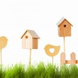 Birdhouses and wooden bird on a background of green grass — Stock Photo #74799509