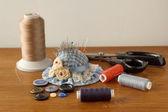Trådar, nålar, knappar, sax på trä bakgrund — Stockfoto