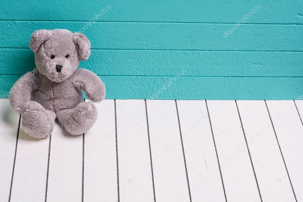 Oso de peluche sentado en el suelo de madera blanco con fondo azul ...