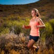 Blonde female trail runner running through a mountain landscape — Stock Photo #70333483