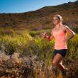 Blonde female trail runner running through a mountain landscape — Stock Photo #70334057