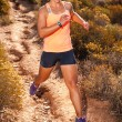 Blonde female trail runner running through a mountain landscape — Stock Photo #70349939