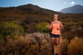 Blonďatá samice stezka běžec běží přes horské krajiny — Stock fotografie