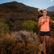 Blonde female trail runner running through a mountain landscape — Stock Photo #70352033