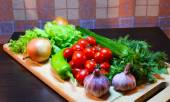 Still life of vegetables and greens on a cutting wooden board — Stock Photo