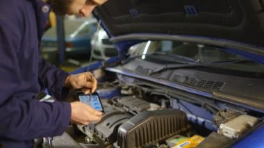 Mechanic entering data into a diagnostic tool while doing routine maintenance on — Stock Video
