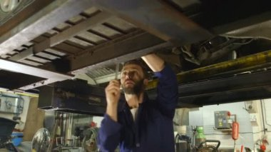 Mechanic inspecting car parts while working under a car — Stock Video