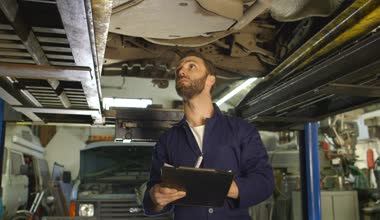 Mechanic inspects the car undercarriage way and takes a note on his inspection — Stock Video