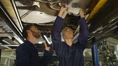 Mechanic supervising his assistant through maintenance and service of a car — Stock Video