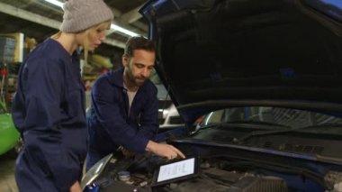 Kfz-Mechaniker und weibliche Auszubildende im Rahmen eines Workshops vor ein Auto — Stockvideo