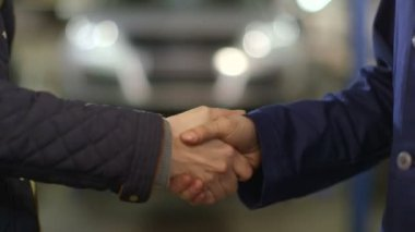 Close Up shot of mechanic and customer shaking hands in an auto repair shop. — Stock Video