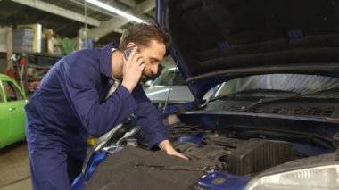 Mechanic talking on a mobile phone with the car owner while repairing a car — Stock Video