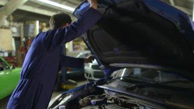 Mechanic closes car hood — Stock Video