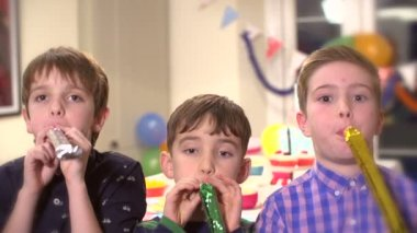 Three young boys blowing party horns towards the camera in slow motion — Stock Video