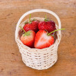 Strawberrys in the basket on wood background — Stockfoto #67781167