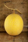Yellow cantaloupe melon on the wooden background — Stock Photo