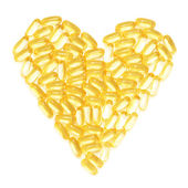 Cod liver fish oil supplements in a healthy heart shape — Stock Photo