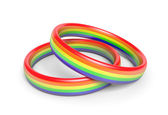 Two wedding rings with rainbow flag colors, a symbol of gay or same sex partnerships — Stock Photo