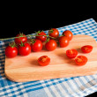 Red tomatoes on cutting board — Stock Photo #64903653