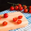 Red tomatoes on cutting board — Stock Photo #64903871