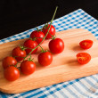 Red tomatoes on cutting board — Stock Photo #64903897